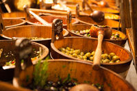 Bowls of various olives for sale at a market place