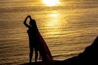 Lovely Brunette Bikini Model Relaxing On The Shoreline At Sunset