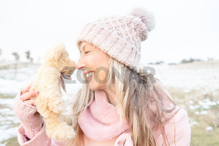 Smiling woman nose to nose with teddy bear