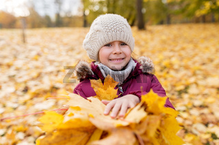 happy girl with fallen maple leaves at autumn park