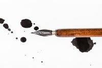 brown dip pen and black ink blots on white paper