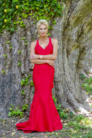 Gorgeous Blonde Model Posing Outdoors Wearing A Red Evening Gown