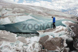 Traveler in a cap and sunglasses is sitting in the snowy mountains on the glacier. Traveler in a natural environment