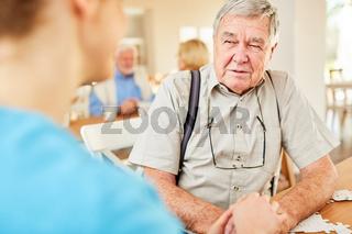 Pflegedienst Frau tröstet Senior Mann im Heim