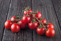 Branches cherry tomatoes on wooden table