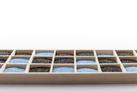 Wooden box with blue and black sand flat angle view