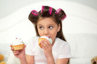 Cute girl eating cupcake.