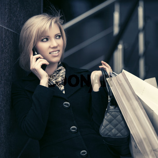Blond fashion woman with shopping bags calling on cell phone