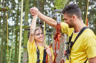 Junges Paar gratuliert sich in einem Kletterkurs