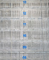 the surface of a concrete service tower core of a building under construction with the floor numbers marked in blue paint