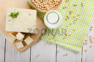 Flat lay of Non-dairy alternatives Soy milk or yogurt in glass bottle and tofu on white wooden table with soybeans in bowl aside