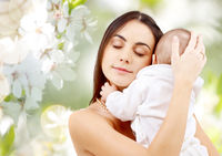 mother with baby over cherry blossom background