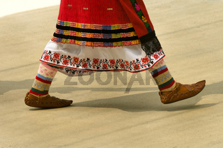 Girls dancing folk dance. People in traditional costumes dance Bulgarian folk dances. Close-up of female legs with traditional shoes, socks and costumes for folk dances. Folklore Dance Festival