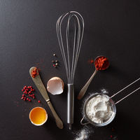 Spoon with red pepper, metal whisk, vintage knife raw egg and flour on a black concrete background with copy space. Concept cooking. Flat lay