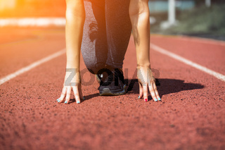 Female Legs in sneakers close-up on pink athletic track