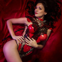 Red silk fabri, beautiful spanish brunette woman with corset of golden and black pieces