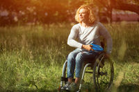 Woman in wheelchair throws frisbee