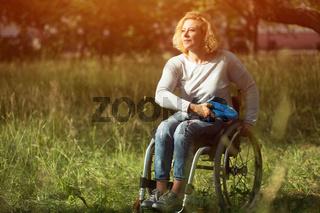 Woman in wheelchair throws frisbee