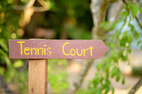 Wooden Signpost Pointing To The Tennis Court