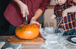 Dad cuts a pumpkin for a pie