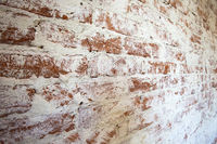 Weathered stained red brick wall background texture peeling plaster