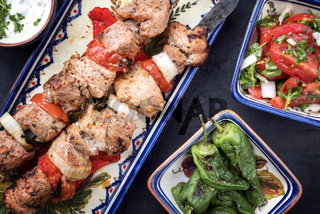 Traditional Greek souvlaki barbecue skewer with tomato onion salad and as closeup on a plate