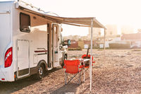 Empty folding chairs and table under canopy near recreational vehicle camper trailer. Adventure