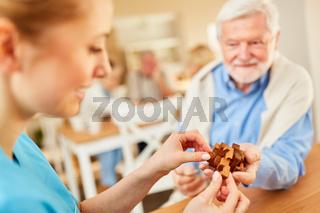 Pflegekraft und Senior mit einem Puzzlespiel