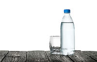 Empty glass and bottle of water