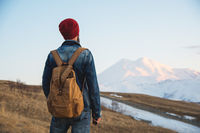 Bearded tourist hipster man in a hat with a backpack stand back on a roadside bump and watching the sunset against the background of a snow capped mountain