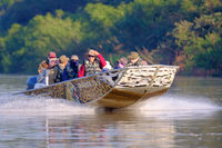 PORTO JOFRE, MATO GROSSO, BRAZIL, JULY 27, 2018: Tourists and guide on boat tour for Jaguar wildlife watching, Pantanal