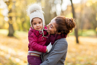happy mother with little daughter at autumn park