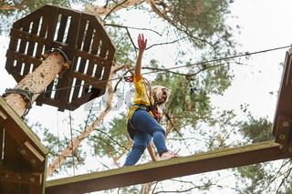 Junge Frau balanciert mutig über ein Hindernis