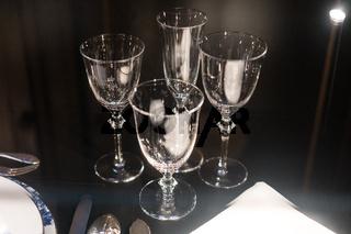 Glasses, forks, knives, napkins on dark black table