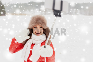 happy woman with selfie stick outdoors in winter