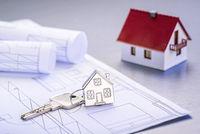 Haus als Schlüsselanhänger auf Bauplänen
