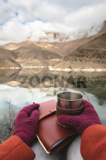 A first-person view of women's hands in coats and mittens are holding a metal mug with tea or coffee and a leather pocket diary against the backdrop of a mountain lake and rocks in the clouds. Travel concept