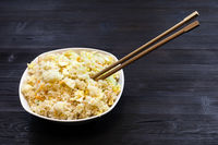 bowl with Fried Rice with chopsticks on dark table