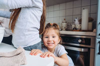 two little girls cook in the kitchen