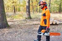 Waldarbeiter mit Motorsäge beim Baum fällen