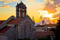 Town of Pula stone church and shipyard cranes sunset view