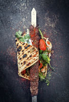 Traditional Adana kebap on a skewer with tomato and yogurt as top view on a flatbread