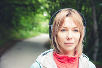 Attractive blond woman in the forest. Close-up portrait of a sporty smiling girl listening to music