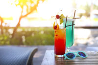 Glass with a bright blue lagoon and tequila sunrise cocktails by the pool