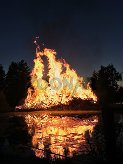 Flammen eines enormen Feuers nachts nahe am See