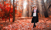 Young girl in autumn forest at sunny day