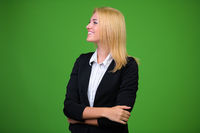 Young beautiful blonde businesswoman against green background