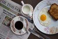 Omelette with roasted bread served on plate as morning breakfast along with news paper, Pune, India.