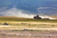 A tractor in the distance kicking up dust