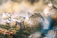 Goldene Christbaumkugeln mit Weihnachtsdekoration